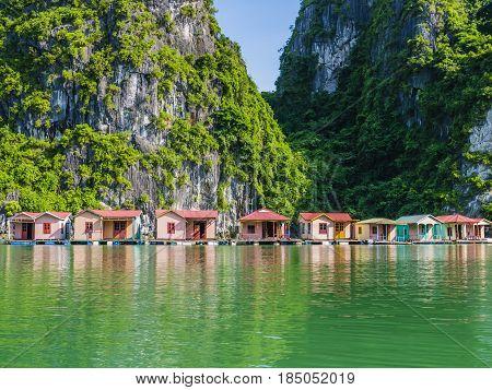 Floating fishing village reflected in emerald waters of Ha Long bay, Vietnam