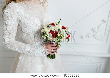 Bride holding bridal bouquet close up. red and white roses, freesia, brunia decorated in composition.