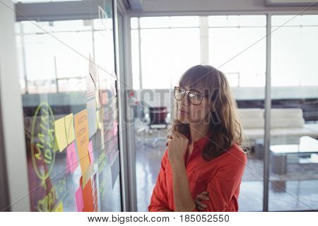 Serious businesswoman looking at adhesive notes on glass in office