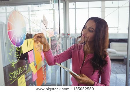 Confident female designer holding adhesive notes on glass in office