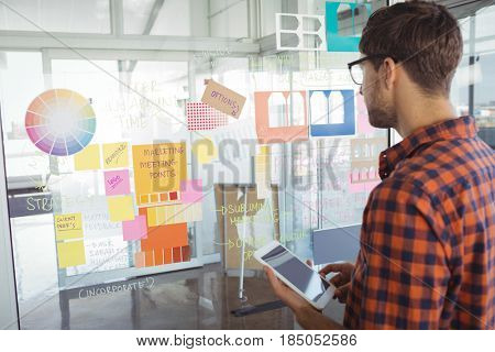 Side view of businessman holding mobile phone while looking at adhesive notes in office