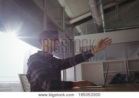 Young businessman gesturing while using virtual reality headset in office on sunny day