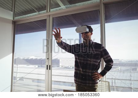 Creative businessman gesturing while experiencing virtual reality in office