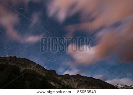 The starry sky with blurred motion colorful clouds and bright moonlight. Expansive night landscape in the European Alps. Vega Star center frame.