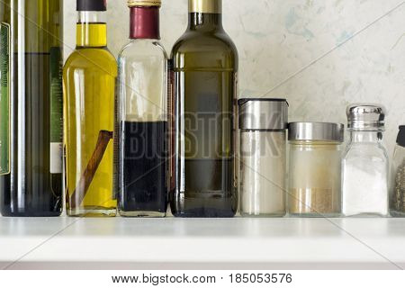 glass bottles of oils jars of condiments salt spices on the shelf