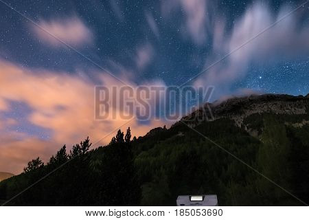 Camper Van Under Moonlight, Starry Sky And Blurred Motion Clouds On The Majestic Alps. Outdoor Activ