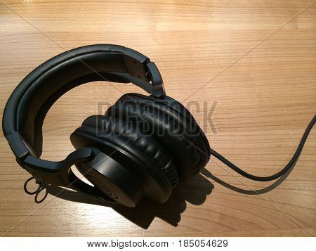 Black and white headphones isolated on brown wooden table in studio background. Sound music headphone. Audio technology accessory Modern electrical earphone gadgets and music concept