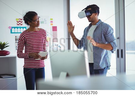 Female colleague assisting businessman while using virtual reality headset in office