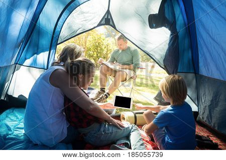 Kids and mother using tablet while father looking at the map at campsite