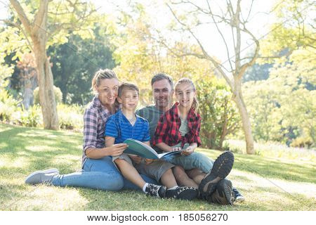 Happy family reading a book in the park on a sunny day