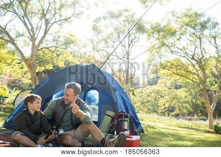 Father and son holding a fishing rod outside the tent while fly fishing