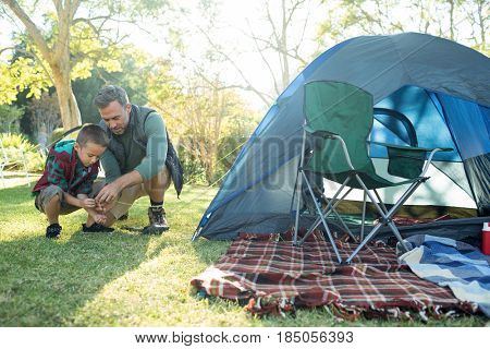 Father and son setting up a tent at campsite