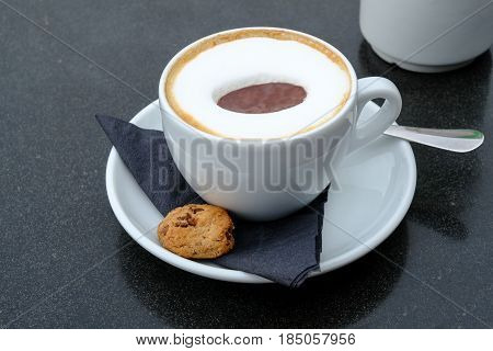 Cup of cappucino coffee in a white cup on a saucer with a biscuit and napkin
