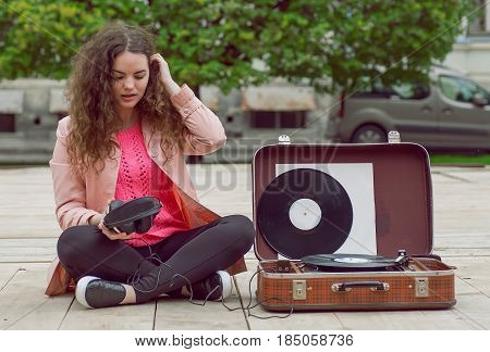 Young girl relaxing in city park and listening music with headphones and a portable stereo vinyl record system.
