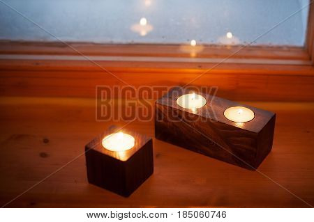 burning candles and candle holders on wooden background