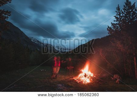 Burning Camp Fire Into Remote Larch And Pine Tree Woodland With High Altitude Landscape And Dramatic