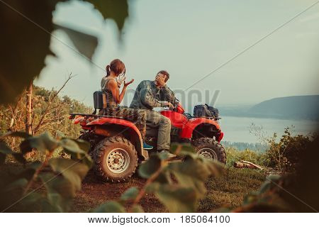 Beautiful Couple Is Discussing The Rout Sitting On A Quadbike