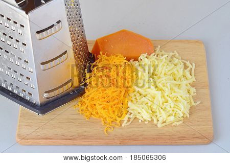 Step by step cooking. Grated gouda and cheddar cheeses with a grater on a wooden cutting board on a gray background