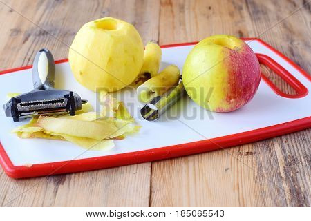 Pealed apples wih the core taken away with special knives on a white cutting board on a wooden background. Step by step cooking. Healthy eating concept