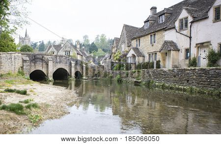 CASTLE COMBE UK - MAY 1 2017: River Bybrook and bridge in Castle Combe Wiltshire UK