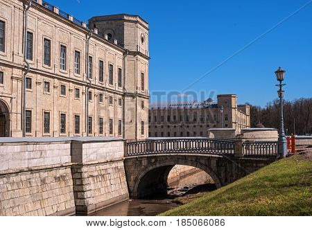 Gatchina Palace. Russia. The left wing of the palace in the foreground. Water ditch and a bridge through it. The bridge is decorated with stylish street lights.