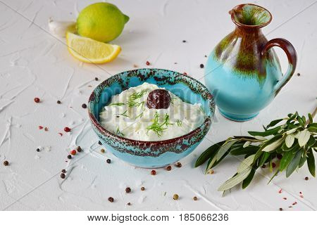 Homemade Greek traditional sauce tzatziki with cucumber, garlic, yogurt , olive oil and lemon in a traditional colored bowl on a white background. Healthy eating concept. Mediterranean lifestyle