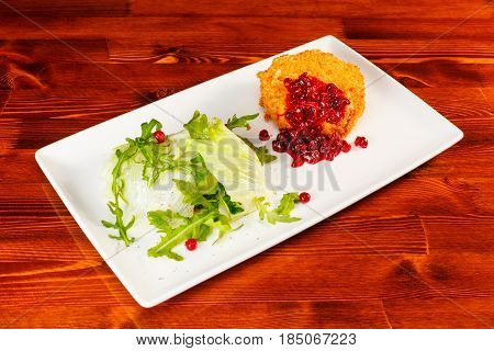 Baked camembert with cranberry sauce and romaine lettuce on big white plate