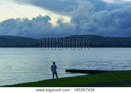 Young man using cell phone at lake Taupo North Island of New Zealand