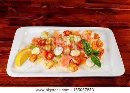 salad of romaine lettuce with smocked salmon quail eggs croutons cherry tomatoes with caesar dressing and grated parmesan on rectangular dish