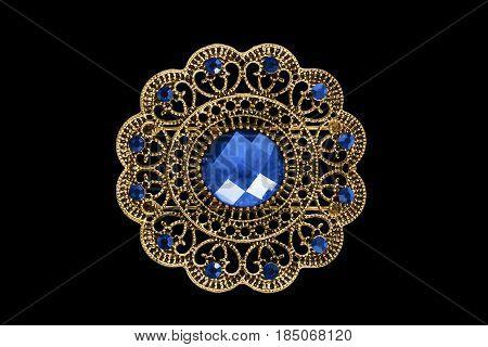 Vintage ethnic gold brooch with blue gems on black background