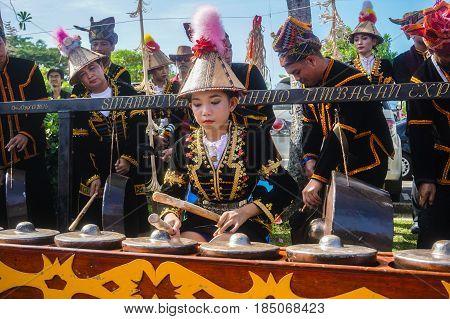 Penampang,Sabah-May 31,2016:Cute girl from kadazandusun ethnic Sabah,Borneo playing gong during Sabah Harvest festival celebration in Kota Kinabalu,Sabah Borneo,Malaysia.