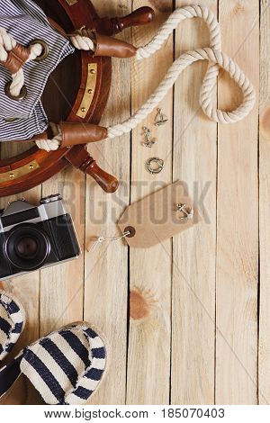 Striped Slippers, Camera, Bag And Maritime Decorations On The Wooden Background