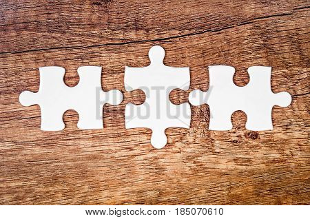 Tree connected jigsaw puzzle pieces on wooden background. The concept of finding the right solutions in teamwork.