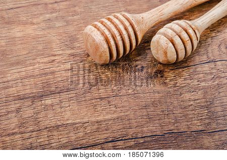 The Wooden honey dippers on wooden background.