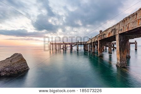 Old pier bridge in beautiful morning sunrise and calmness seascape at Khao Laem Ya National park Rayong Province Eastern Thailand