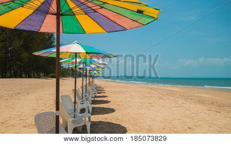 white lounge chairs with colorful sun umbrella on beach with blue sky