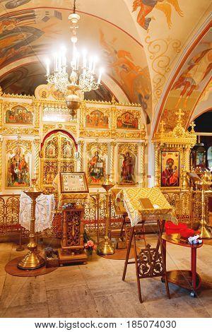 Golden religious utensils - Bible cross prayer book missal baptismal font. Interoior of Orthodox Christian Church. Russia.