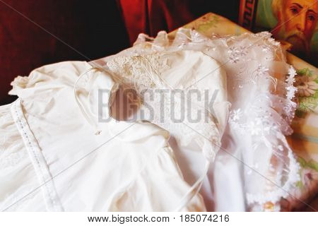 Laced dress for christening. Elegant outfit for little girl. Russian Orthodox church ceremony details.
