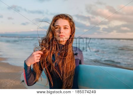 Young sexy woman with long hairs and wetsuit. Posing with surf board near ocean at sunset. Ready for surfing. Close up