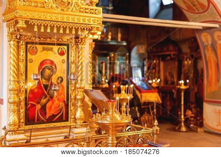 Golden candleholder and icons traditional interior of Orthodox church. Russia.
