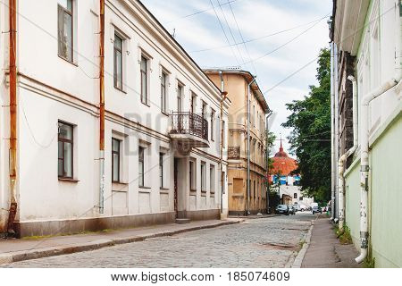 Old houses in Vyborg Russia. Buildings with old fashioned windows and downpipes. Round Tower in the end of street.