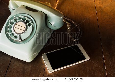 Two Phone Different Technology. Modern Mobile Phone And Old Vintage Classic Telephone On Wooden Tabl