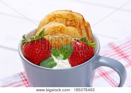 cup of american pancakes with white yogurt and fresh strawberries on checkered dishtowel - close up