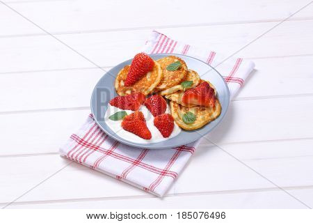plate of american pancakes with white yogurt and fresh strawberries on checkered dishtowel