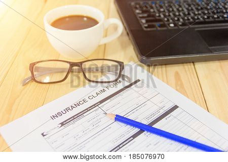 Blue pencil eyeglasses coffee cup and insurance claim form on the table. A blank form is waiting to be completed / filled and signed by a policyholder.