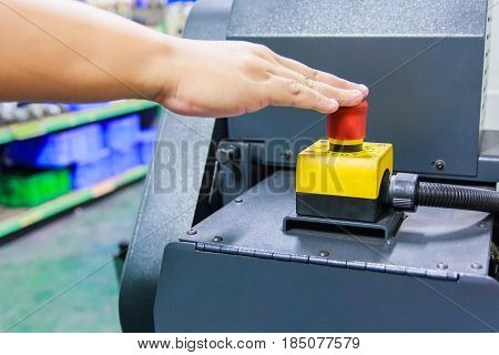 Finger push on red emergency stop switch for safety of lathe machine in factory workshop.