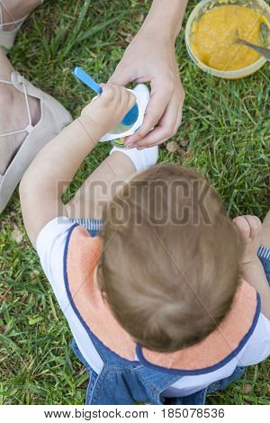 2 year-old boy eating a yoghurt sitting on the grass. He is been helped by his mother