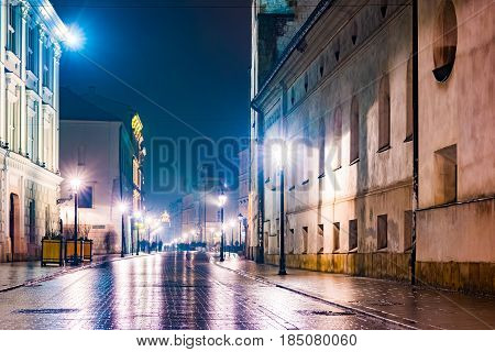Night street in the Krakow, Poland. Colorful night illumination reflecting in the wet stone pavement of the old town. Beautiful background photo.