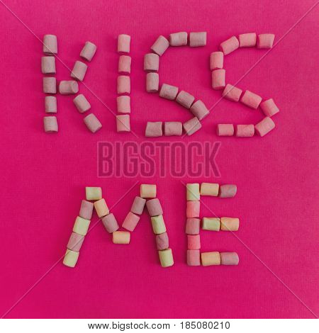 Marshmallows Background with colorful marshmallows Multicolored marshmallows are lying out in the form of the inscription Kiss me Pink background