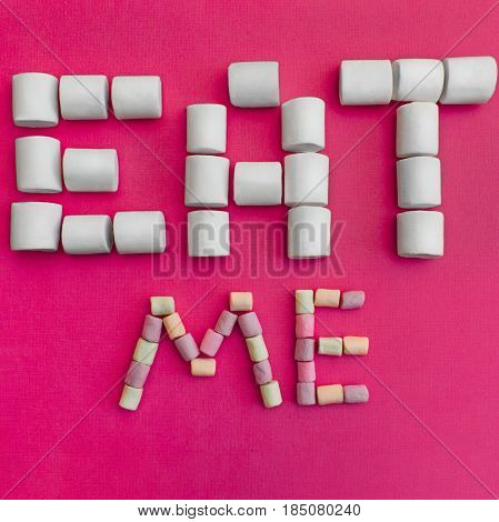 Marshmallows Background with colorful marshmallows Multicolored marshmallows are lying out in the form of the inscription Eat me Pink background